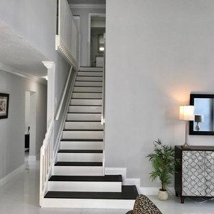 Imagen de escalera recta, clásica renovada, grande, con escalones de madera pintada, contrahuellas de madera pintada y barandilla de madera