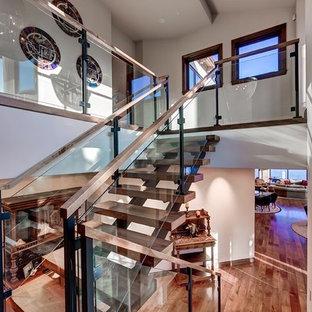 Ejemplo de escalera en U, de estilo americano, con barandilla de vidrio