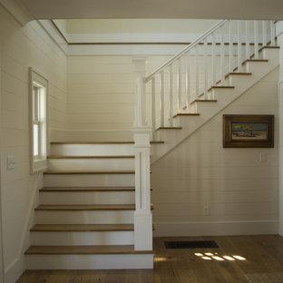 Diseño de escalera en L, tradicional, grande, con escalones de madera, contrahuellas de madera pintada y barandilla de madera