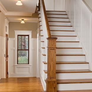 Immagine di una scala a rampa dritta stile americano di medie dimensioni con pedata in legno, alzata in legno verniciato e parapetto in legno