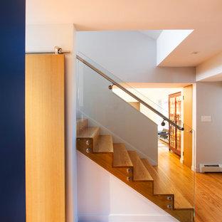 Ejemplo de escalera recta, minimalista, de tamaño medio, con escalones de madera, contrahuellas de madera y barandilla de vidrio