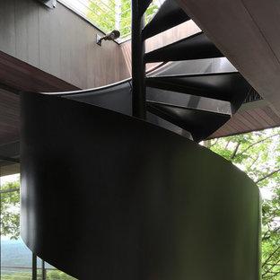 ニューヨークの中くらいの金属製のミッドセンチュリースタイルのおしゃれならせん階段 (金属の蹴込み板) の写真
