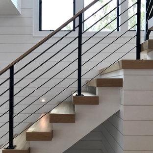 Foto de escalera en L y machihembrado, minimalista, de tamaño medio, sin contrahuella, con escalones de madera, barandilla de metal y machihembrado