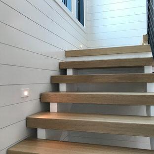 Diseño de escalera en L y machihembrado, de tamaño medio, sin contrahuella, con escalones de madera, barandilla de metal y machihembrado