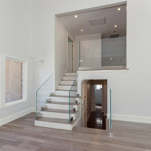 Example of a mid-sized minimalist wooden straight glass railing staircase design in Los Angeles with painted risers