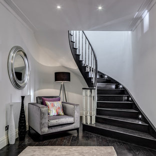Trendy painted curved staircase photo in London with painted risers