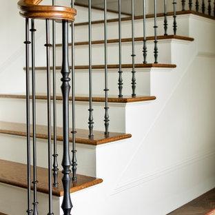Ejemplo de escalera en U, tradicional, de tamaño medio, con escalones de madera, contrahuellas de madera pintada y barandilla de varios materiales