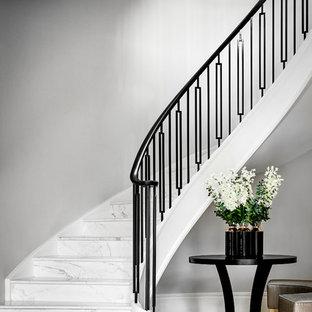 Ispirazione per un'ampia scala a chiocciola design con pedata in marmo e parapetto in metallo