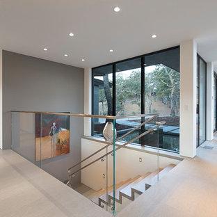 Modelo de escalera en U, actual, extra grande, con escalones de travertino, contrahuellas de travertino y barandilla de vidrio