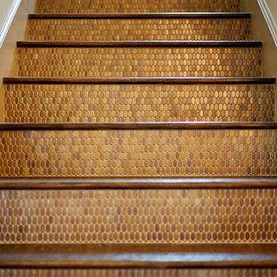 Ejemplo de escalera recta, clásica renovada, extra grande, con escalones de madera, contrahuellas con baldosas y/o azulejos y barandilla de metal