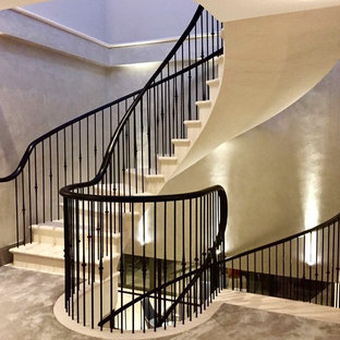 Example of a mid-sized trendy limestone curved staircase design in Kent with limestone risers