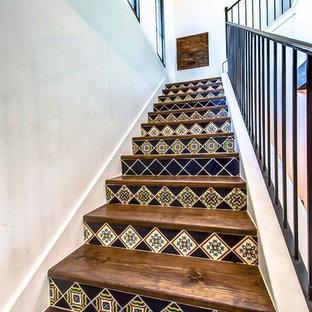 """Immagine di una piccola scala a """"L"""" stile americano con alzata piastrellata, pedata in legno e parapetto in metallo"""