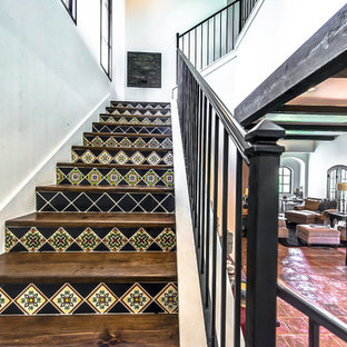 Large southwest wooden metal railing staircase photo in Austin with tile risers