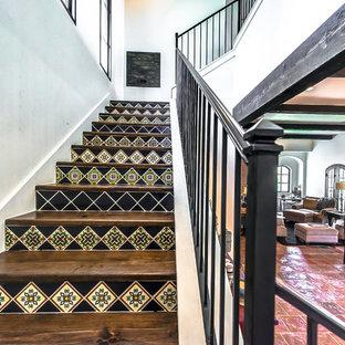 Modelo de escalera de estilo americano, grande, con escalones de madera, contrahuellas con baldosas y/o azulejos y barandilla de metal
