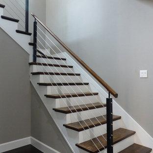 Foto de escalera en L, contemporánea, de tamaño medio, con escalones de madera, contrahuellas de madera pintada y barandilla de cable
