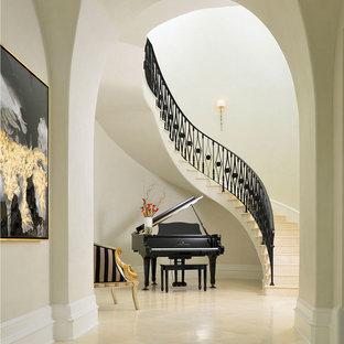 Diseño de escalera curva, mediterránea, extra grande, con barandilla de metal, escalones de piedra caliza y contrahuellas de piedra caliza