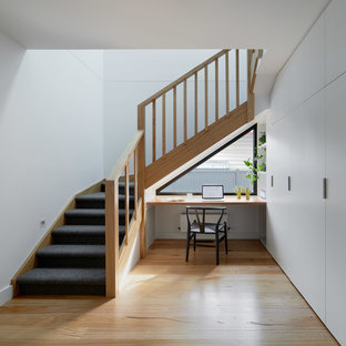 Photo of a large contemporary carpeted l-shaped staircase in Melbourne with carpet risers and wood railing.