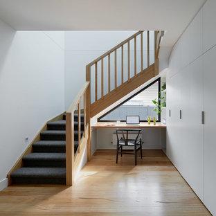 メルボルンの大きいカーペット敷きのコンテンポラリースタイルのおしゃれなかね折れ階段 (カーペット張りの蹴込み板、木材の手すり) の写真