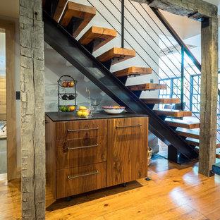 Modelo de escalera recta, rústica, de tamaño medio, sin contrahuella, con escalones de madera y barandilla de metal