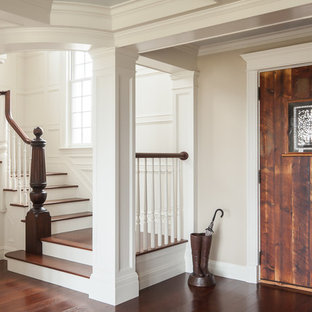 Example of a beach style wooden staircase design in Portland Maine with painted risers