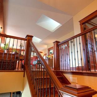 """Foto di una grande scala a """"U"""" stile americano con pedata in legno, alzata in legno e parapetto in legno"""