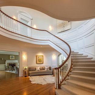 Идея дизайна: огромная лестница в классическом стиле с деревянными ступенями и крашенными деревянными подступенками