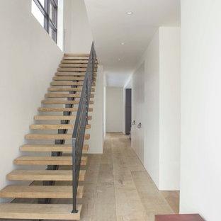 Foto på en stor funkis flytande trappa i trä, med sättsteg i metall