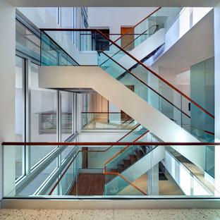 Imagen de escalera minimalista, grande, con escalones de madera y barandilla de vidrio