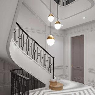 Modelo de escalera de caracol y panelado, tradicional renovada, grande, con escalones de madera, contrahuellas de madera, barandilla de metal y panelado