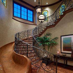 Imagen de escalera curva, mediterránea, grande, con escalones de madera, contrahuellas con baldosas y/o azulejos y barandilla de metal