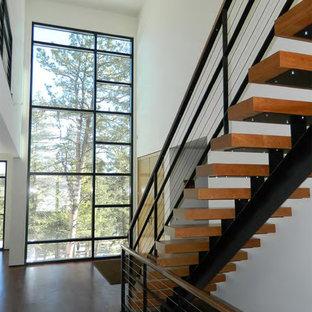 Cette photo montre un escalier sans contremarche droit tendance avec des marches en bois et un garde-corps en câble.