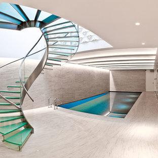 Ejemplo de escalera curva, actual, con escalones de vidrio, contrahuellas de vidrio y barandilla de vidrio