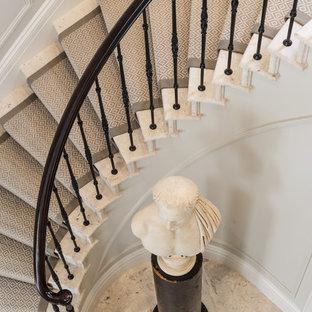 Bild på en funkis svängd trappa i marmor, med sättsteg i marmor