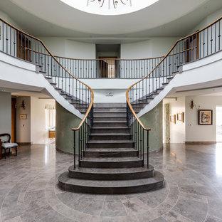 Пример оригинального дизайна интерьера: изогнутая лестница в классическом стиле с ступенями из плитки, подступенками из плитки и деревянными перилами