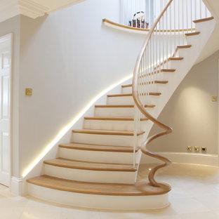 Imagen de escalera curva, clásica renovada, con escalones de madera y contrahuellas de madera pintada