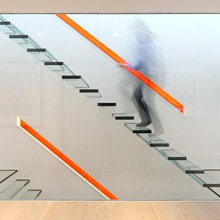 Design ideas for a medium sized modern glass staircase in London with open risers.