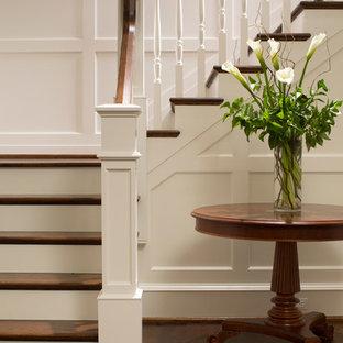 ボルチモアの巨大な木のトラディショナルスタイルのおしゃれなかね折れ階段 (木の蹴込み板) の写真