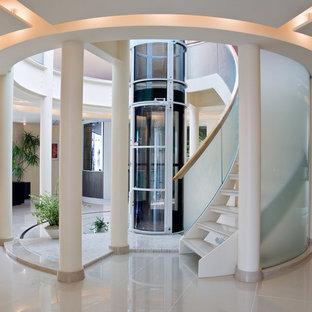 Idéer för en stor modern svängd trappa i akryl, med öppna sättsteg och räcke i glas