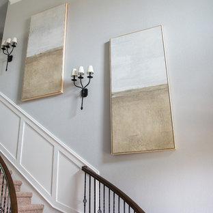 Exempel på en stor shabby chic-inspirerad svängd trappa i trä, med sättsteg i målat trä och räcke i metall