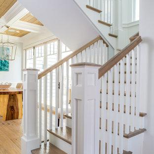 Imagen de escalera en U, costera, pequeña, con escalones de madera, contrahuellas de madera pintada y barandilla de madera