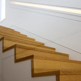Immagine di una scala a rampa dritta minimalista con pedata in legno e alzata in vetro