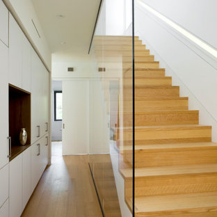 Idee per una scala a rampa dritta moderna con pedata in legno e alzata in vetro