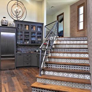 Ejemplo de escalera recta, industrial, de tamaño medio, con escalones de madera, contrahuellas con baldosas y/o azulejos y barandilla de cable