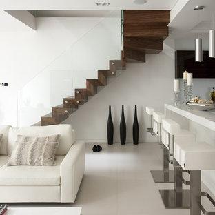 Ejemplo de escalera suspendida, minimalista, con escalones de madera, contrahuellas de madera y barandilla de vidrio