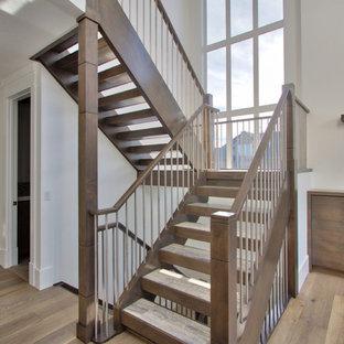 """Foto di una grande scala a """"L"""" minimalista con pedata in marmo e alzata in legno"""