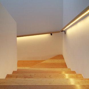 他の地域の小さいコンクリートのコンテンポラリースタイルのおしゃれな折り返し階段 (木の蹴込み板) の写真