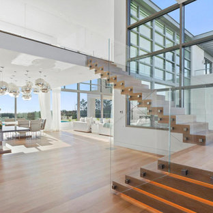 Staircase - large contemporary wooden l-shaped glass railing staircase idea in New York with wooden risers