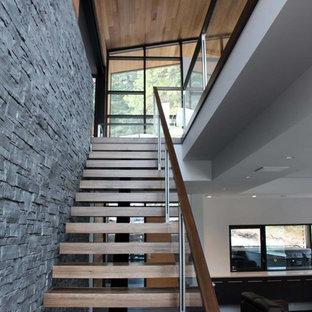 Diseño de escalera en L, moderna, de tamaño medio, con escalones de madera, contrahuellas de madera y barandilla de vidrio