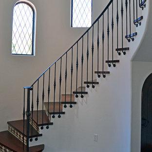 Diseño de escalera curva, clásica, con escalones de madera y contrahuellas con baldosas y/o azulejos