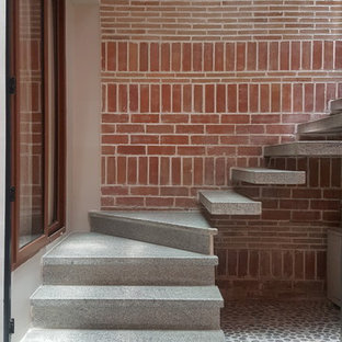 Imagen de escalera curva, actual, con escalones de hormigón y contrahuellas de hormigón